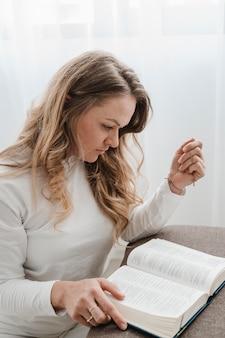 Vista laterale della donna che legge dalla bibbia a casa