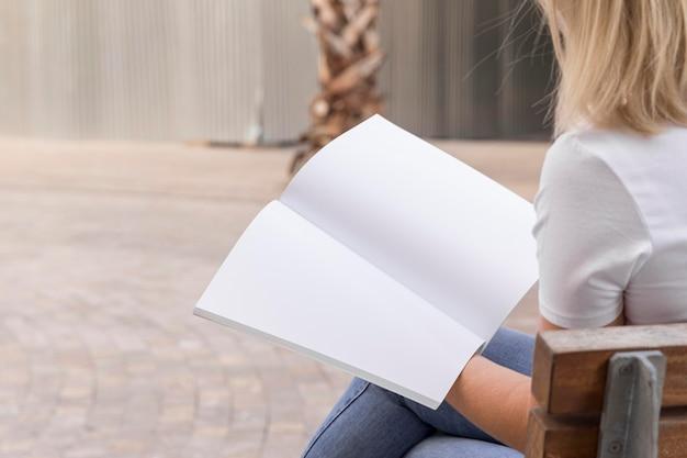 Vista laterale della donna che legge il suo libro all'aperto con spazio di copia