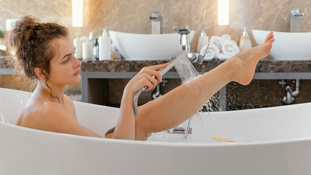 Side view woman relaxing in bathtub