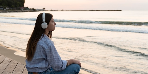 Donna di vista laterale che si distende sulla spiaggia con lo spazio della copia