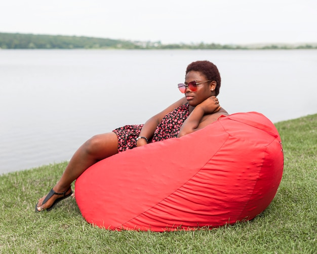 Side view of woman relaxing outside on bean bag