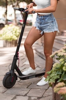 Side view of woman riding electric scooter outdoors
