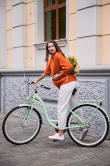 Side view of woman riding her bicycle outdoors with bouquet of flowers