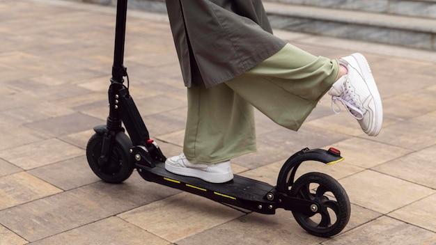 Vista laterale della donna che guida il suo scooter elettrico all'aperto