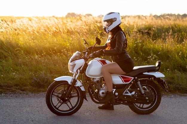 Side view of woman riding motorcycle with helmet on