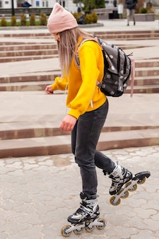 Side view of woman rollerblading on pavement