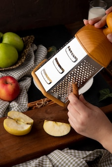 Side view a woman rubs cinnamon on a grater on apple on a board