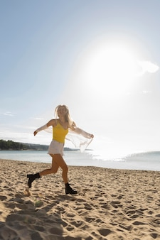 Side view of woman running on beach