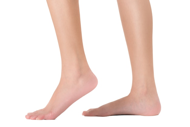 Side view of woman's feet in walking pose, isolated on white background.