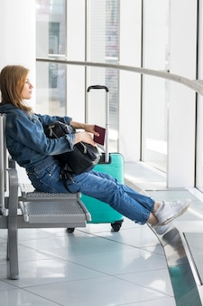 Side view of woman sitting in airport