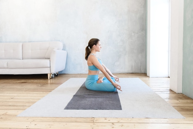 側面図蓮華座に座って、マットの上で自宅でヨガで瞑想している女性