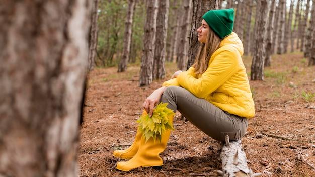 森の中に座っているサイドビュー女性
