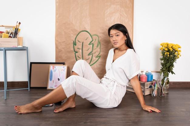 Вид сбоку женщина, сидящая на полу