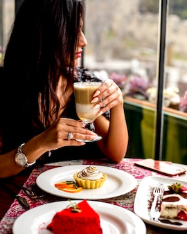 Side view of a woman sitting at the table with a glass of coffee latte macchiato