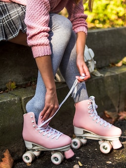 Side view of woman in socks putting on roller skates