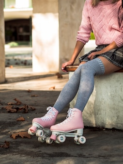 Side view of woman in socks and skirt with roller skates