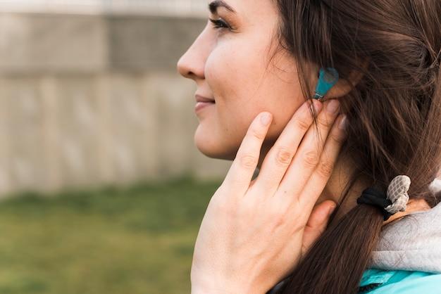 Side view woman in sportswear listening to music