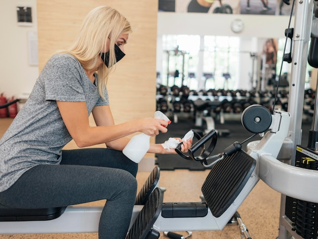 Side view of woman spraying disinfectant on gym equipment