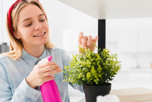 Side view woman spraying plant