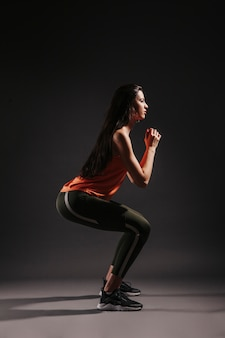 Side view woman squatting on dark background
