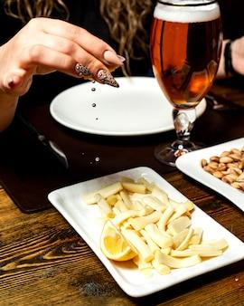 Vista laterale di una donna che schiaccia il succo di limone sul formaggio a pasta filata sul piatto