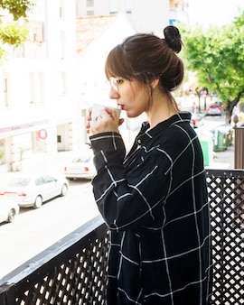 Side view of a woman standing in balcony drinking coffee