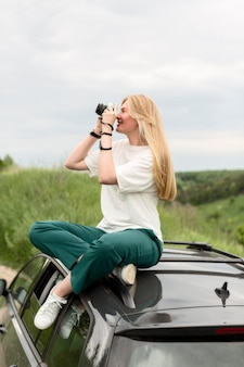 Side view of woman standing on car and taking nature pictures