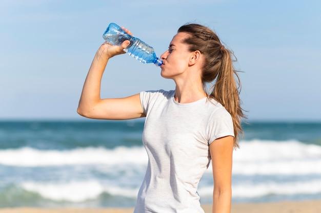 Vista laterale della donna che rimane idratata durante l'allenamento in spiaggia