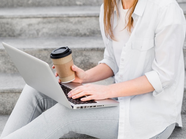 Side view of woman on steps with coffee and laptop