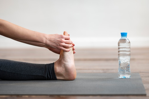 Side view of woman stretching on yoga mat with water bottle