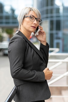 Side view woman in suit talking over phone