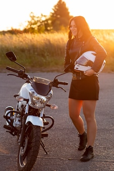 Side view of woman in the sunset next to motorcycle holding helmet