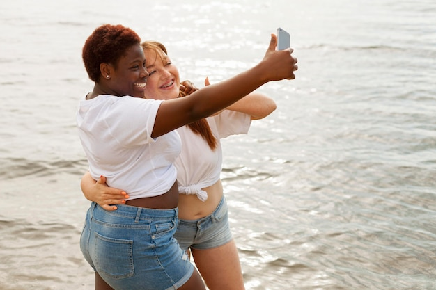 Side view of woman taking selfie at the beach