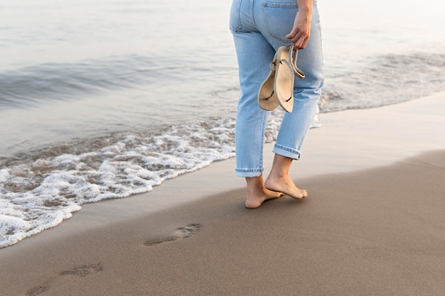 Side view of woman taking a walk by the beach
