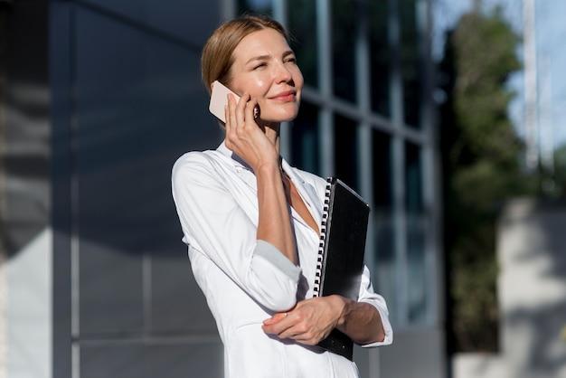 Donna di vista laterale che parla sul telefono esterno