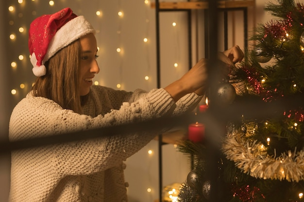 Vista laterale della donna attraverso la finestra che decora l'albero di natale