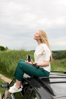 Side view of woman on top of car holding camera