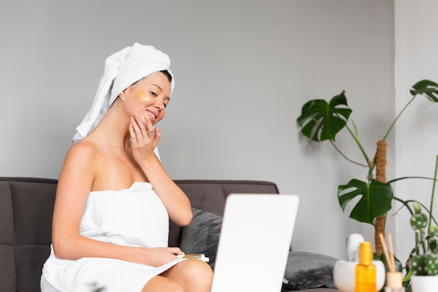 Side view of woman in towel applying skincare