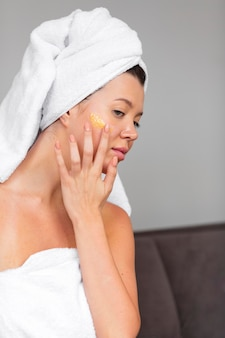 Vista laterale della donna in asciugamano utilizzando la cura della pelle