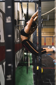 Side view of woman training on bar