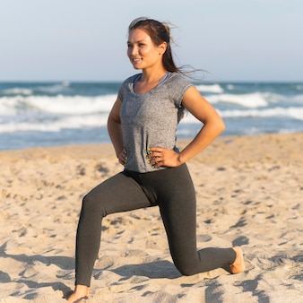 Side view of woman training on the beach