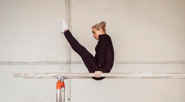 Тренировка женщины для чемпионата по гимнастике, вид сбоку
