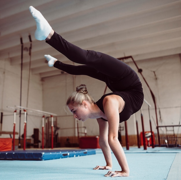 Тренировка женщины на олимпийских играх по гимнастике, вид сбоку