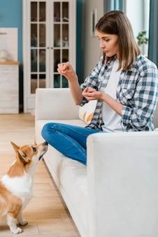 Vista laterale della donna che prepara il suo cane con gli ossequi