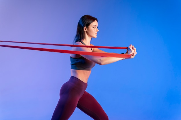 Side view woman training with elastic band