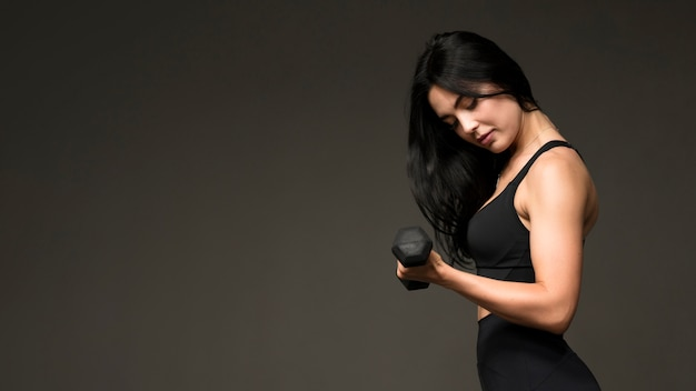 Side view woman training with hands weights