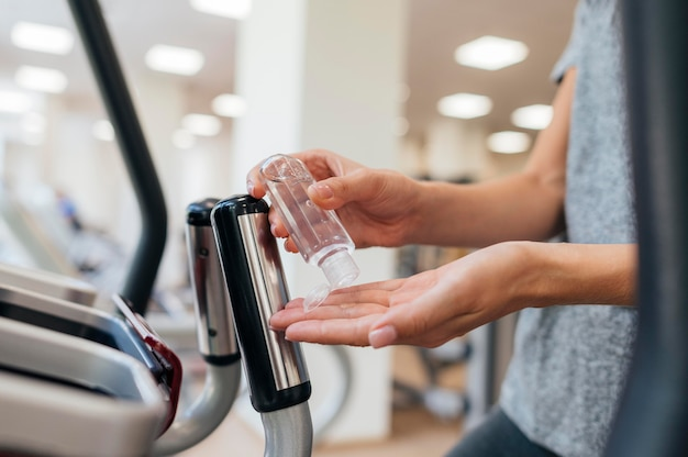 Side view of woman using hand sanitizer at the gym during pandemic