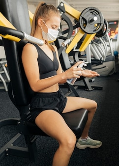 Side view of woman using hand sanitizer while working out at the gym