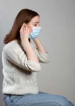Side view of woman using a medical mask for protection