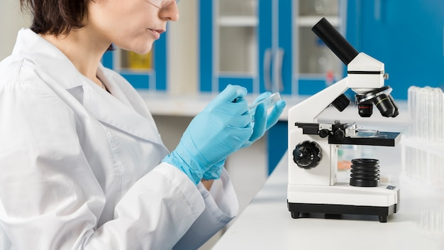 Side view woman using a microscope